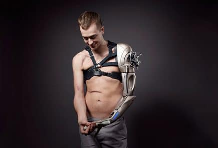 Sophie De Oliveira Barata, lead designer for the Alternative Limbs Project, developed a 3D printed arm inspired by Metal Gear Solid. Int he photo, the wearer proudly shows it off, complete with a chest strap from the game.