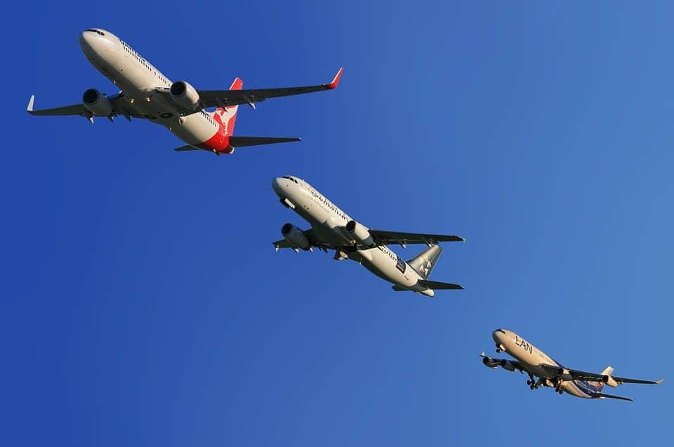 Three planes fly in a row against a clear blue sky